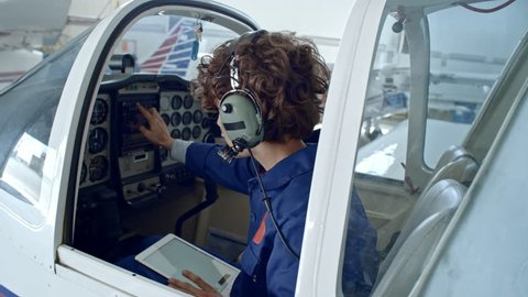 Tilt down of female pilot with headset sitting in cabin of jet airplane in hangar, using digital tablet and checking cockpit