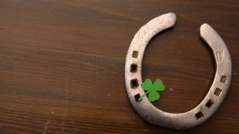 holidays and st patrick's day concept - horseshoe with shamrock on wooden background