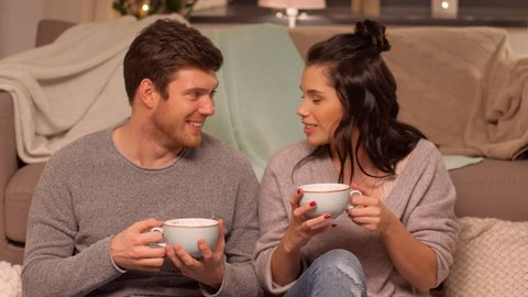 hygge, leisure and people concept - happy couple drinking cacao with marshmallow at home