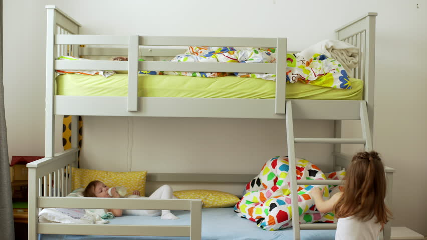 Picture of small two children resting in bedroom and lying in bunk bed with colorful bedding after awakening in morning