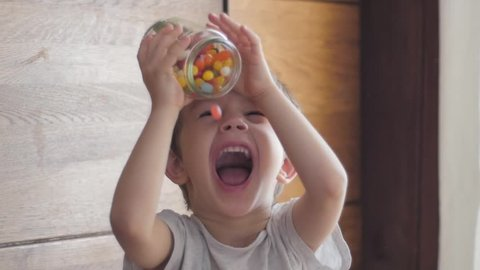 boy eating candies falling from jar