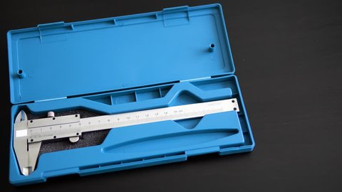 Measuring device. Slide caliper in a blue box. The man opens a box with the appliance. Decimal system of measurements. Accuracy of measurements. 4K. Calipers.