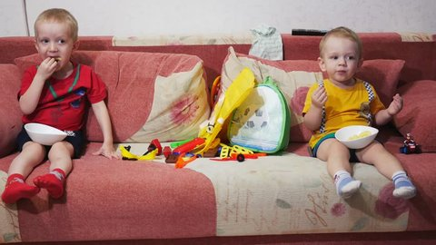 The brothers sit on the sofa at home and watch TV. Eat corn sticks and smile