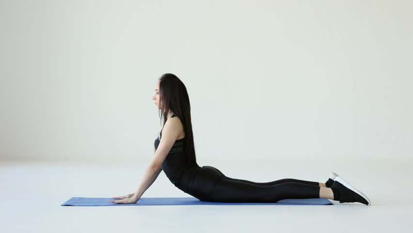 The young charming athletic sport woman doing the side bridge on the exercise mat at the white background. Fitness tutorials for beginners.