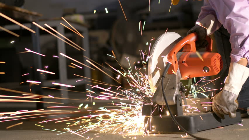 Man hard worked and sawing steel. Worker using cutter circular metal has lighting spark. Concept of engineering, workshop, industry, manufacture and business.