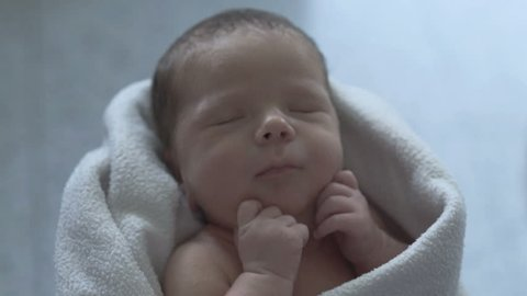 Adorable newborn baby sleeping in a blanket and holds his mother's hand