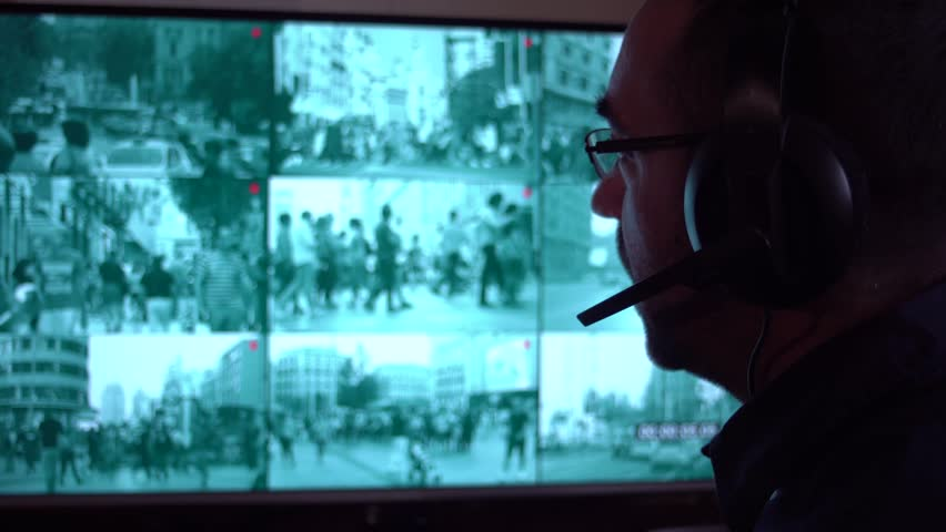 Security officer watching monitoring displays in control room. Security cameras. Security surveillance system monitor. Security worker in control room taking calls via headsets | Shutterstock HD Video #1007313160