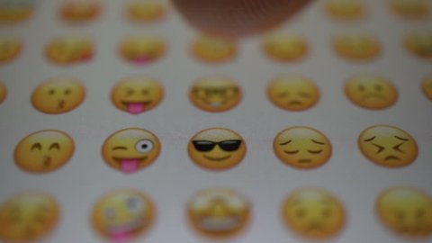 Samara, Russia - February 6, 2018: man looks at the emoji icons on a iphone. Emoji is a graphic language, where pictures are used instead of words