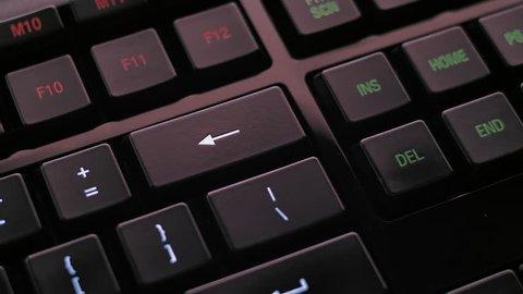 Man pressing backspace or delete key on modern illuminated computer keyboard.