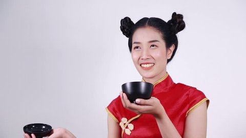 happy woman wearing chinese cheongsam dress with chopsticks and bowl