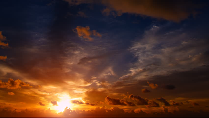 Dramatic sunset in firey shades of orange and blue. with puffy. drifting clouds silhouetted against the sky. Video 1080p