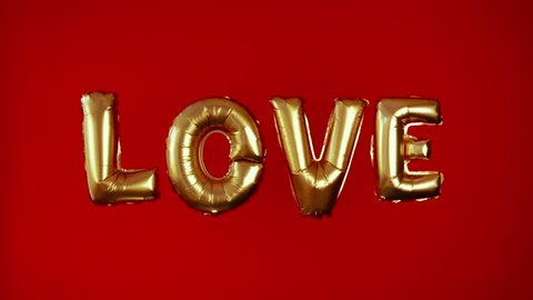 The word LOVE is in large airy gold letters on a red background. Inflatable balls in the shape of the word love. A declaration of love. Volumetric letters. Congratulations on Valentine's Day, wedding.