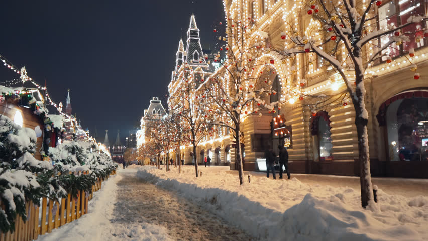 Beautiful Red Square New Year winter decorations, steady camera shot along night shining pedestrian street in the center of Moscow, trees with bright lights and balls are covered with snow.