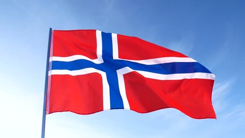 Red with blue cross Norwegian national flag is slowly waving in the blue clear sky on white flagpole.