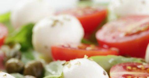 caprese salad with mini mozzarella balls, tomatoes and capers