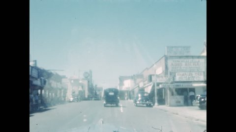 1940s: Car enters border town. Road sign for Route 83 in Texas. Car drives down desert rural highway. Lookout with graffiti. Car turns on to road.