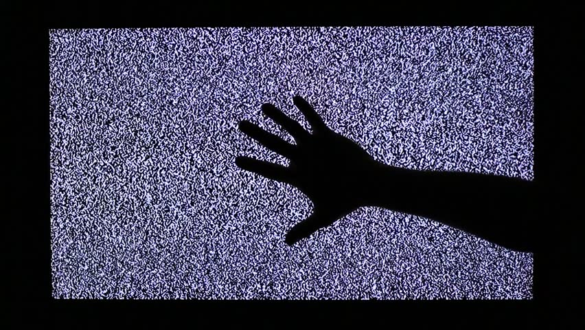TV channel noise and black hand on television screen
