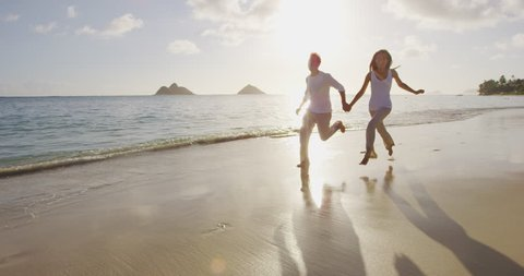Vacation Couple at beach at sunset romantic holding hands running playful. Young couple in love enjoying romance in casual elegant clothing on luxury beach vacation travel holidays. Slow motion.