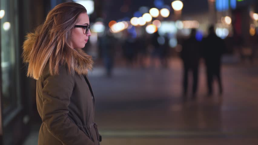 Young woman checking her smart watch at night, in the street, downtown