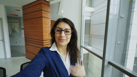 POV of young businesswoman in suit taking a selfie photo holding smartphone and have fun in modern office