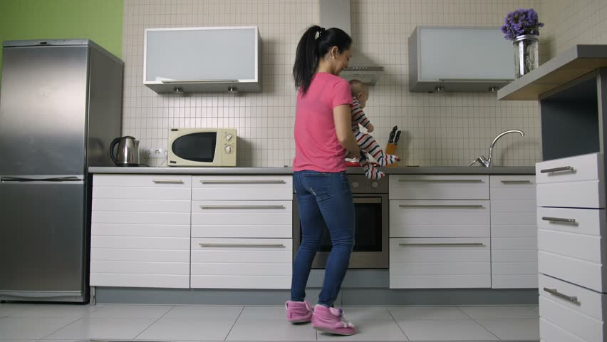 Busy beautiful hispanic mother holding her baby son and cooking food in the kitchen at home. Young woman rushing and running around to finish meal preparation and house work on time. Dolly shot