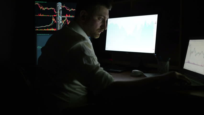 Stockbroker in white shirt is working in a dark monitoring room with display screens. Stock Exchange Trading Forex Finance Graphic Concept. Businessmen trading stocks online.