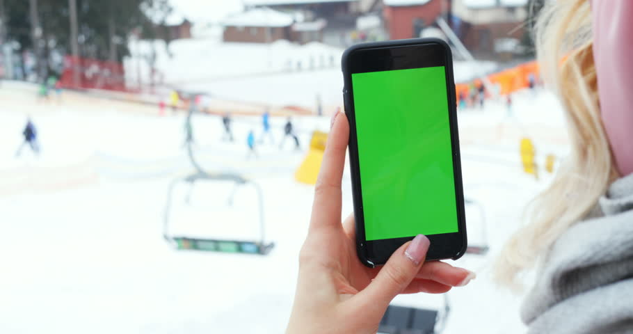 Close up female hand holding smart phone using mobile tapping scrolling blank green screen chroma key mock-up pointing finger touchscreen blur snow winter skiing people background ski lifts resort | Shutterstock HD Video #1007530624