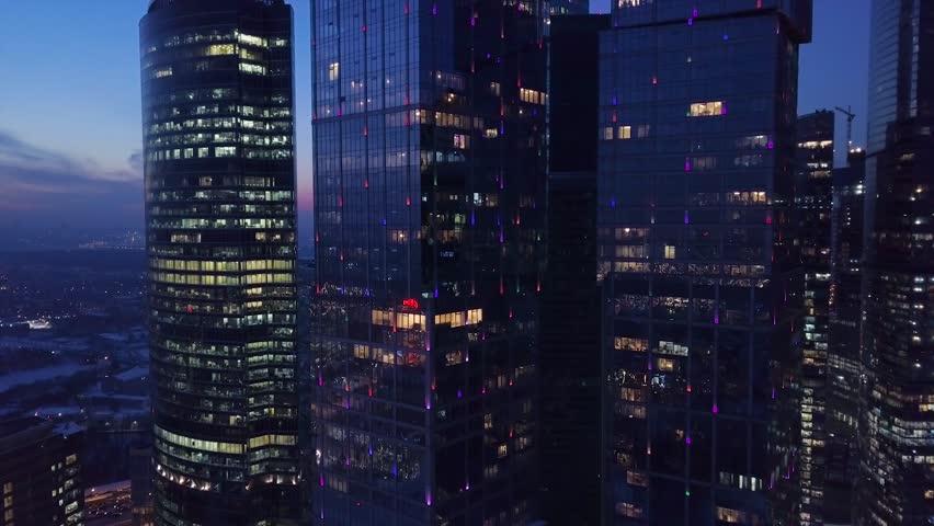 Futuristic illuminated night city aerial approach close to skyscrapers | Shutterstock HD Video #1007535970