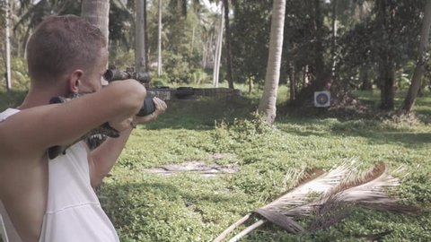 man in white jacket is shooting from a crossbow