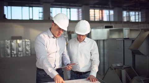 Two employees male engineers discussing work with tablet computer at logistics center warehouse factory.  Construction engineer working, architects businessman man engineer builder contractor indoors