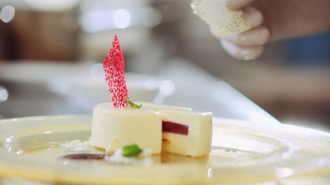 Close up view of confectioner's hand putting a chocolate garnish decoration on the top of vanilla mousse pastry desert. Luxury cuisine, delicious, top
