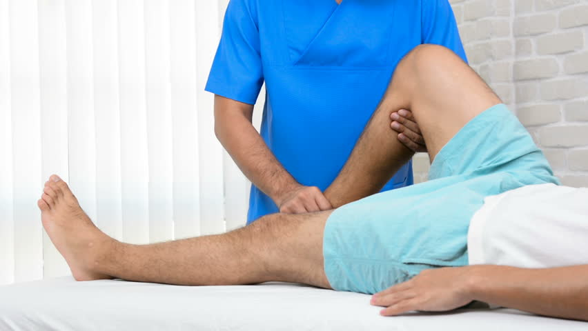 Physiotherapist training rehab exercise to broken leg patient on the bed in hospital