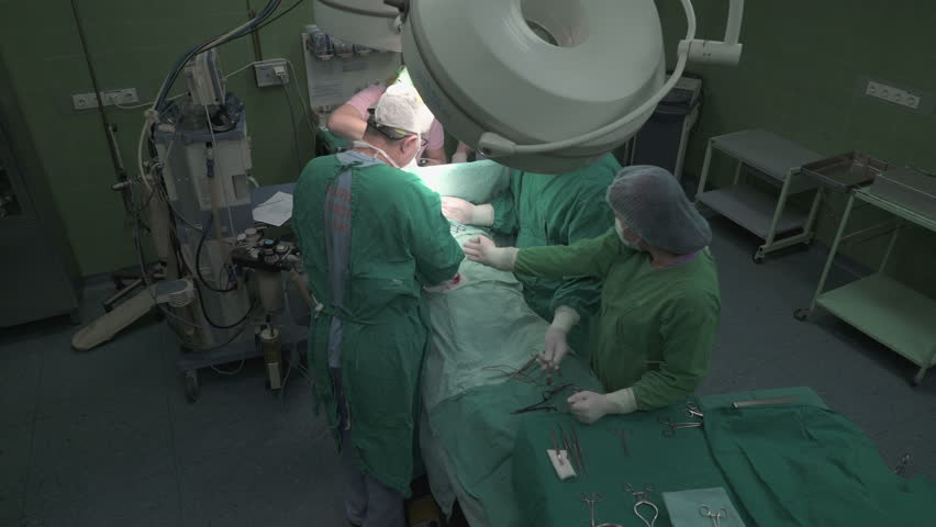 A team of senior surgeons, medical technicians and anesthesiologist using surgical tools and instruments to operating patient in operation theater, wide angle view, crane shot, steady cam, real scene.