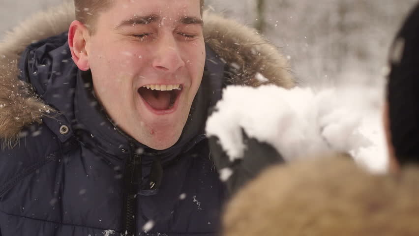Girl blowing on face of her boyfriend snow, close-up, slow motion. The girl blows snow on her boyfriend