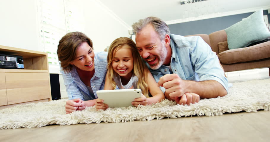 Family lying on rug and using digital tablet in living room | Shutterstock HD Video #1007579620