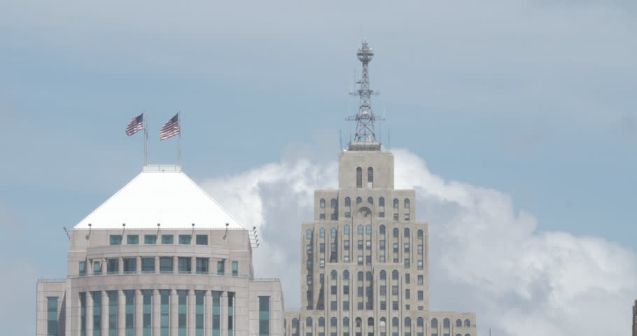 Close up of rooftops and American Flags atop the West Jefferson and Penobscot buildings in downtown Detroit, Michigan.