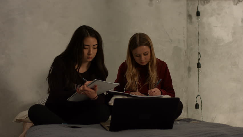 Charming high school diverse female students studying together at home and chatting while sitting cross-legged with textbooks and laptop on bed. Cheerful girls writing notes while doing their homework | Shutterstock HD Video #1007583523