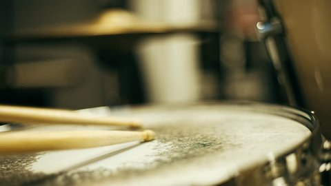 Close up vintage cinema look video of drum playing, young ruck drummer playing on the old drums with wooden sticks, snare and hi-hat