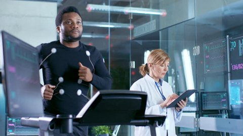 Male Athlete Runs on a Treadmill with Electrodes Attached to His Body while Sport Scientist Holds Tablet and Supervises EKG Status. Laboratory with High-Tech Equipment. Shot on RED EPIC-W 8K Camera.