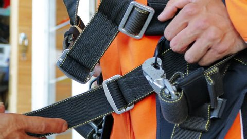 Parachute jumping,skydiving activity. Instructor controlling and fixing harness before the flight for person's safety. Effective parachute equipment. Extreme sport