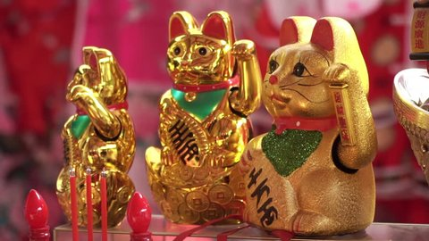 Slow motion of Golden Japanese Lucky Cat. Maneki neko or beckoning cat in the shop. Beckoning cats are placed in front of shops for good luck and attracting customers.