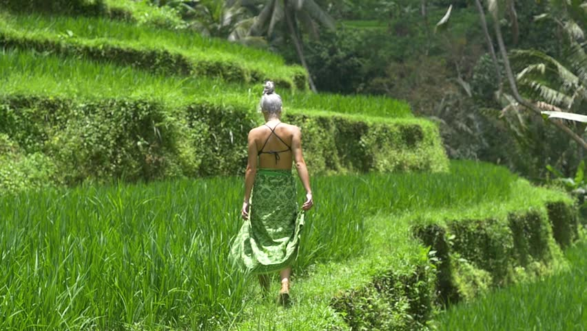 Slow motion of Caucasian millennial female walking rice paddy path | Shutterstock HD Video #1007636851