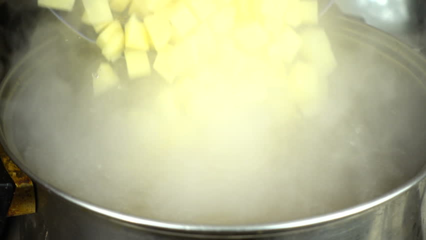 Preparation of soup. Pour the potatoes into the broth. Slow Motion.