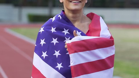 Full of happiness athlete woman holding flag of USA and enjoying victory slow-mo