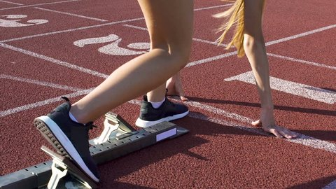 Track runner woman preparing to run at starting blocks, active workout, slow-mo