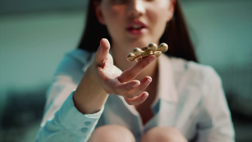 Close up shot of a woman's hands, a pretty woman is engaged in a fashionable affair; she is twirling a popular toy in her hands, called a spinner | Shutterstock HD Video #1007646883