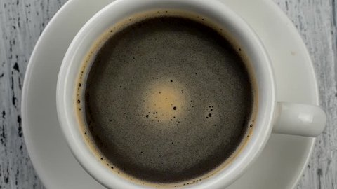 Coffee foam swirls in white cup with coffee. Shabby white wooden background. Top down view.