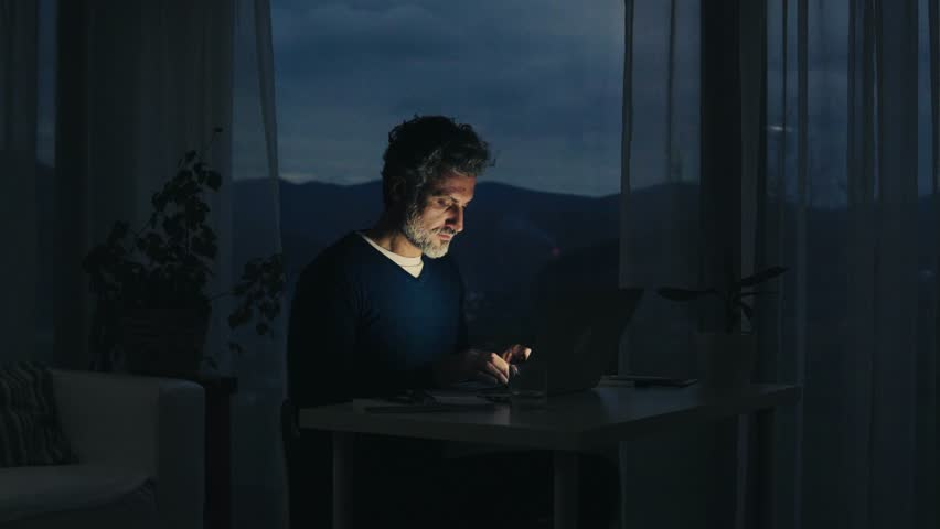 A mature man with laptop working in home office. | Shutterstock HD Video #1007661340