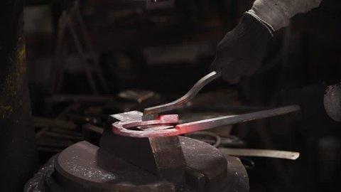 Blacksmith is fixing stamp over heated horseshoe on a stand of heavy automatical hammer. Jackhammer is beating and master is taking out a product.