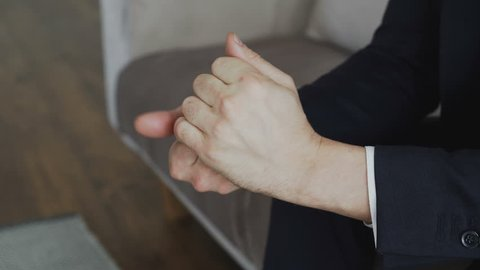 Close-up of businessman nervously moving hands before meetting with psychologist in office